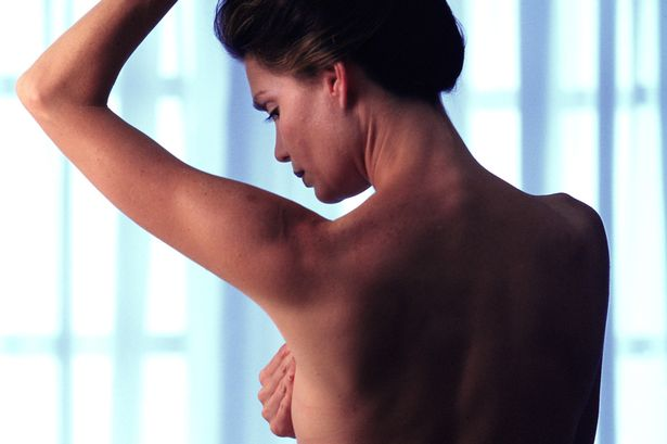 Woman-examining-breasts-for-abnormal-growths-rear-view