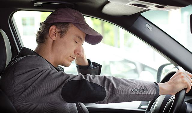 Bored, tired man sleeping at the wheel of his car