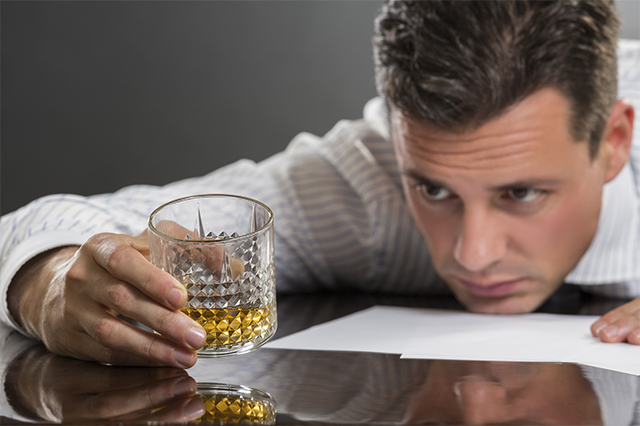 Portrait of sad frustrated young businessman resting his chin on a table while looking at the glass of alcohol in his hand. Selective focus on the glass.