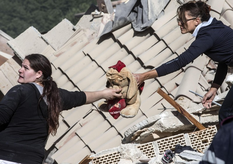 epa05508460 Two woman hold a peluche in Amatrice, central Italy, 24 Augut 2016, following a 6.2 magnitude earthquake, according to the United States Geological Survey (USGS), that struck at around 3:30 am local time (1:30 am GMT). The quake was felt across a broad section of central Italy, in Umbria, Lazio and Marche Regions, including the capital Rome where people in homes in the historic center felt a long swaying followed by aftershocks. According to reports at least 37 people died in the quake. EPA/MASSIMO PERCOSSI