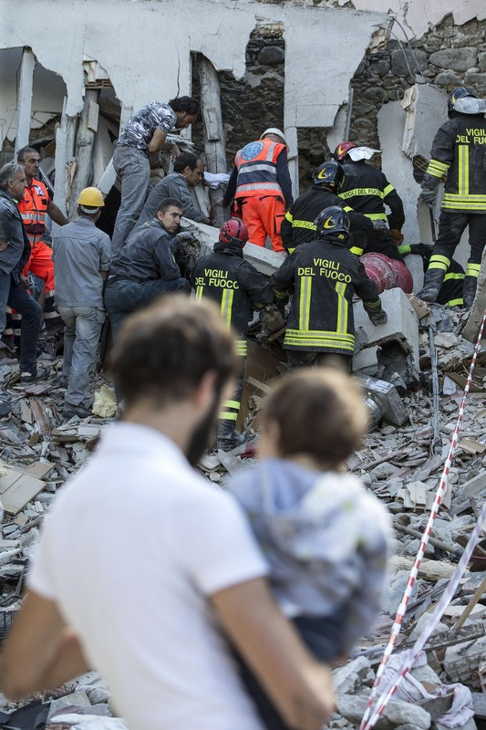epa05508720 Rescuers of the local fire department work to pull a victim from the rubble of a collapsed building in Fonte del Campo near Accumoli, central Italy, 24 August 2016, following a 6.2 magnitude earthquake, according to the United States Geological Survey (USGS), that struck at around 3:30 am local time (1:30 am GMT). The quake was felt across a broad section of central Italy, in Umbria, Lazio and Marche Regions, including the capital Rome where people in homes in the historic center felt a long swaying followed by aftershocks. According to reports at least 38 people died in the quake. EPA/ANGELO CARCONI