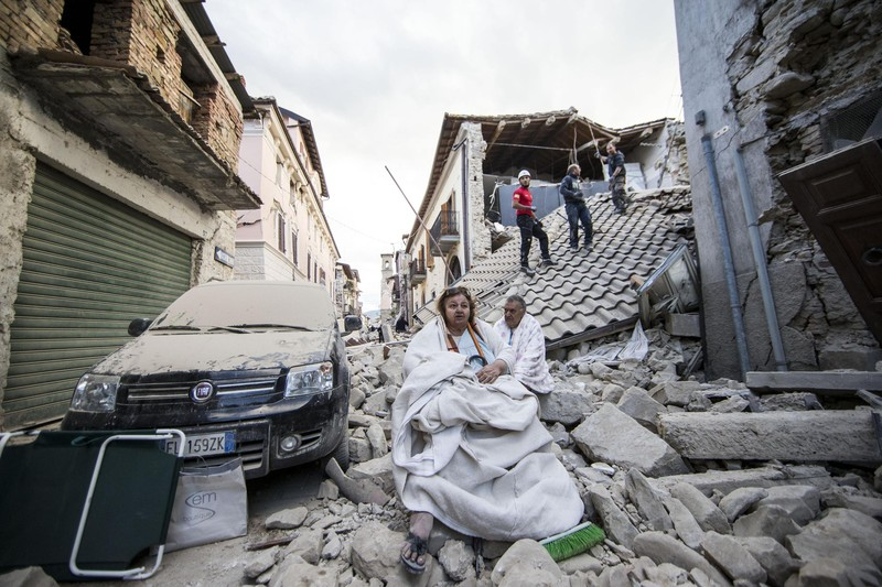 epaselect epa05508230 Residents look on as they stand on the rubble of collapsed buildings in Amatrice, central Italy, 24 August 2016, following a 6.2 magnitude earthquake, according to the United States Geological Survey (USGS), that struck at around 3:30 am local time (1:30 am GMT). The quake was felt across a broad section of central Italy, including the capital Rome where people in homes in the historic center felt a long swaying followed by aftershocks. According to reports at least 21 people died in the quake, 11 in Lazio and 10 in Marche regions. EPA/MASSIMO PERCOSSI