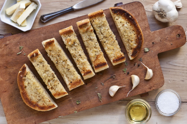 Garlic Bread Sliced on a Wooden Cutting Board; From Above; Ingredients for Garlic Bread